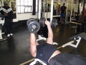 Male doing flat dumbbell press - UP